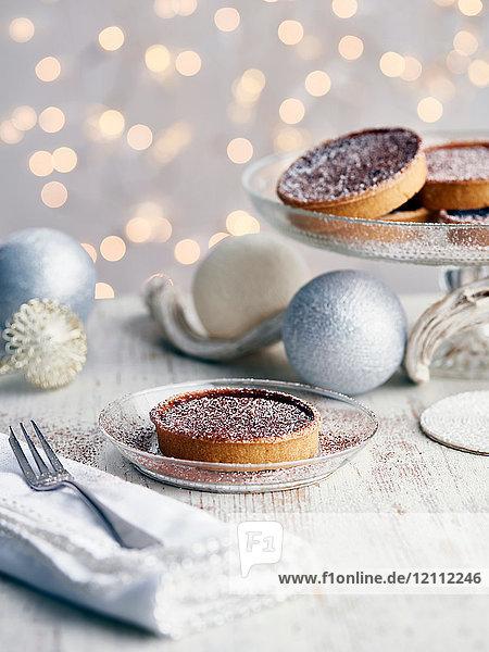 Mit Zucker bestäubte Weihnachtskuchen  daneben Weihnachtskugeln
