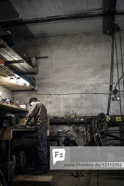 Mechanic working at bench with dismantled vintage motorcycle in workshop