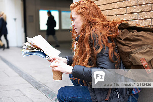Young woman sitting outdoors  holding coffee cup  looking at map