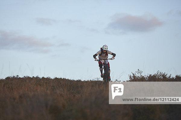 Männlicher Mountainbiker radelt durchs Moor