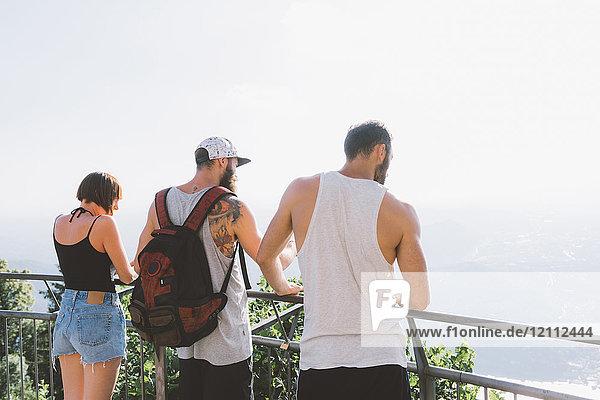 Drei junge Hipster-Freunde schauen vom Balkon auf den Comer See  Como  Lombardei  Italien