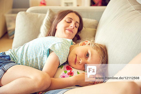 Portrait of girl hugging and resting on pregnant mother's stomach
