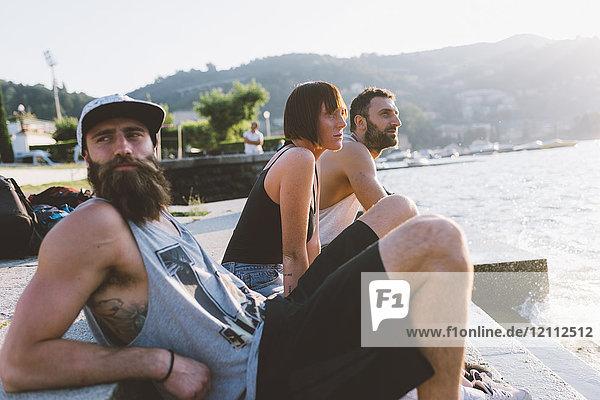 Drei junge Hipster sitzen mit Blick auf den Comer See  Como  Lombardei  Italien