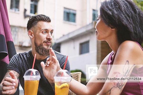 Ein multiethnisches Hipster-Paar unterhält sich in einem Straßencafé  Shanghai Französische Konzession  Shanghai  China