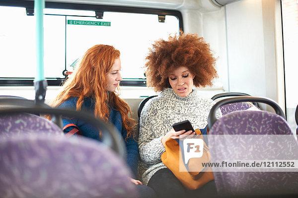 Zwei junge Frauen sitzen im Bus und schauen auf ein Smartphone
