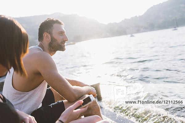 Junges Paar am Wasser sitzend  Comer See  Lombardei  Italien
