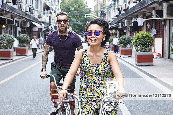 Multi ethnic hipster couple cycling along city street  Shanghai French Concession  Shanghai  China