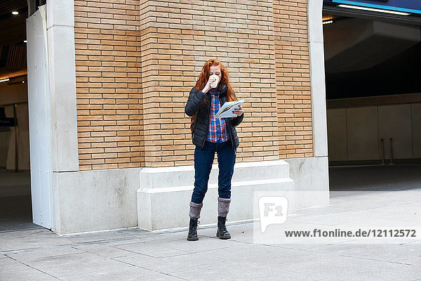 Young woman standing in street  drinking coffee  holding map