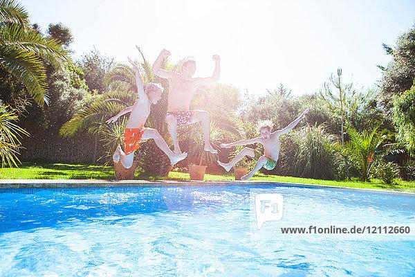 Vater und Söhne springen in der Luft in ein Freibad