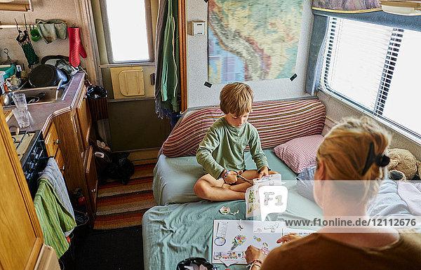 Mutter und Sohn beim Ausschneiden von Bildern im Wohnmobil  Chuquisaca  Bolivien  Südamerika