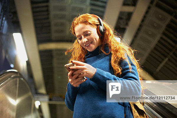 Young woman on escalator  looking at smartphone  low angle view