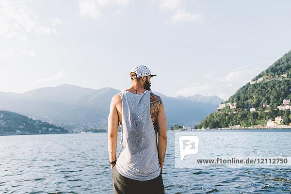 Rückansicht eines jungen Hipster-Männchens  das vom Wasser aus schaut  Comer See  Lombardei  Italien