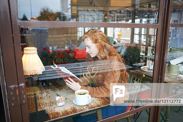 View through window of woman in coffee shop reading