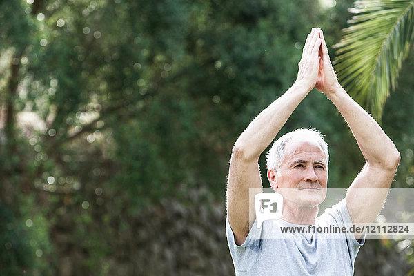 Mann  Hände zusammen  Arme in Yogastellung erhoben