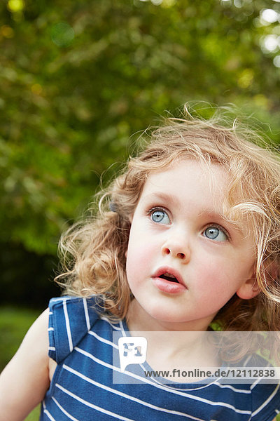 Portrait of blond wavy haired girl with blue eyes gazing in park
