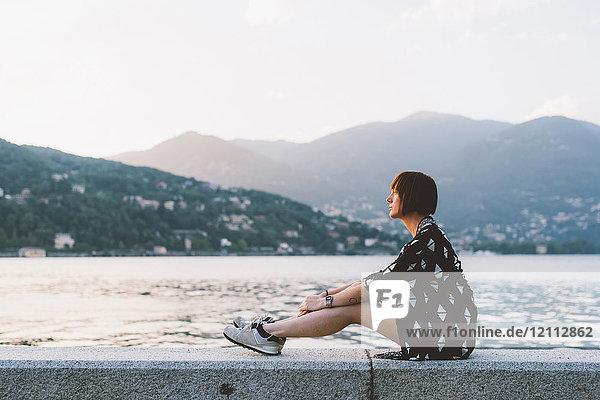 Junge Frau sitzt an der Uferpromenade des Comer Sees  Lombardei  Italien