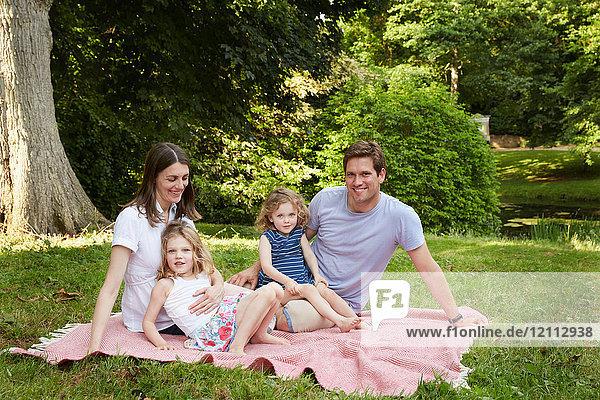 Porträt mittelgroßer Eltern und zwei Töchter auf Picknickdecke im Park