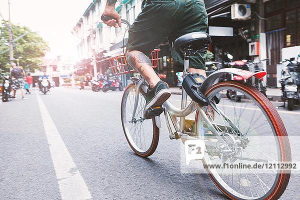 Taille eines jungen männlichen Hipsters  der mit dem Fahrrad die Stadtstraße entlang fährt  Shanghai French Concession  Shanghai  China