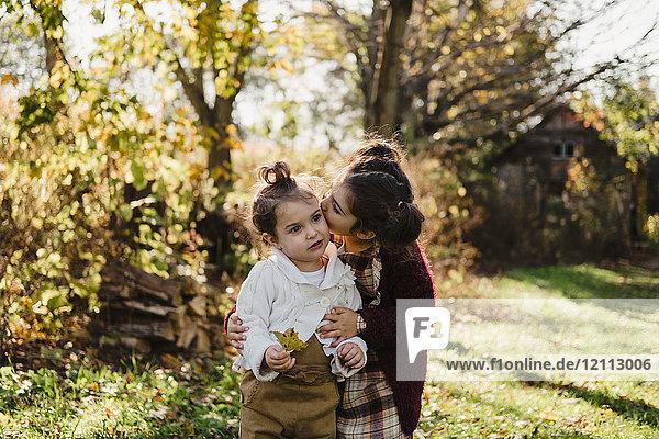Mädchen umarmt jüngere Schwester  in ländlicher Umgebung