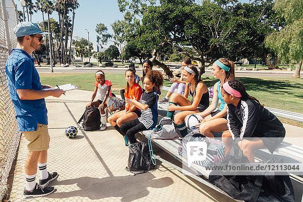 Teacher instructing schoolgirl soccer players on school sports field bench