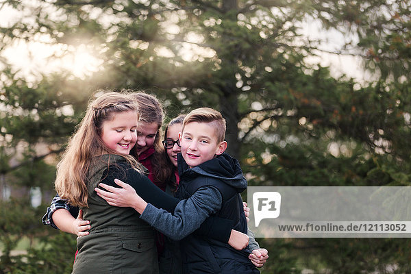 Portrait of boy and female cousins hugging in garden