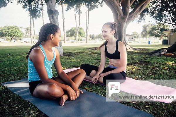Two schoolgirls chatting on yoga mats on school sports field