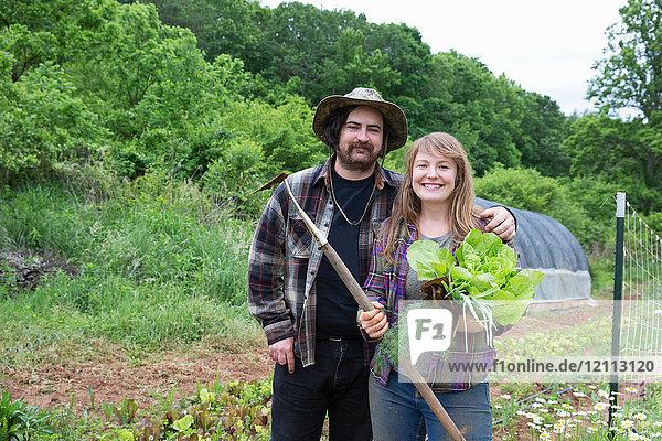 Ehepaar im Gemüsegarten schaut lächelnd in die Kamera