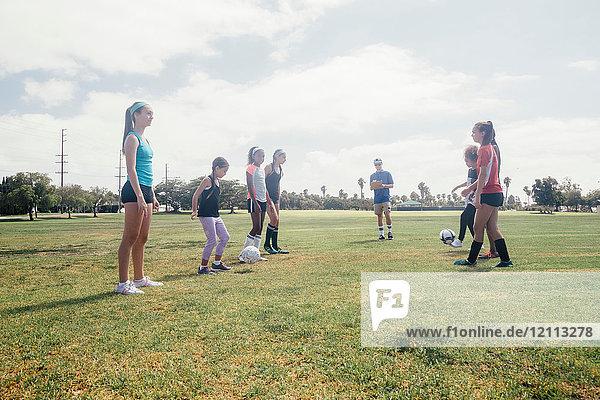 Schulmädchen treten sich auf dem Schulsportplatz Auge in Auge einen Fussball zu