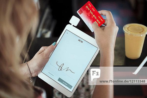Über-Schulter-Ansicht einer jungen Frau mit digitalem Tablett und Kreditkarte