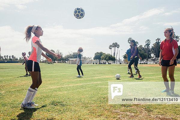 Schulmädchen treten sich auf dem Schulsportplatz einen Fussball von Angesicht zu Angesicht