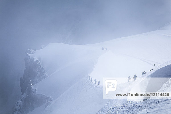 Mountain climbers are heading to Mont Blanc in fog  viewed from Aiguille du midi; Chamonix-Mont-Blanc  Haute-Savoie  France