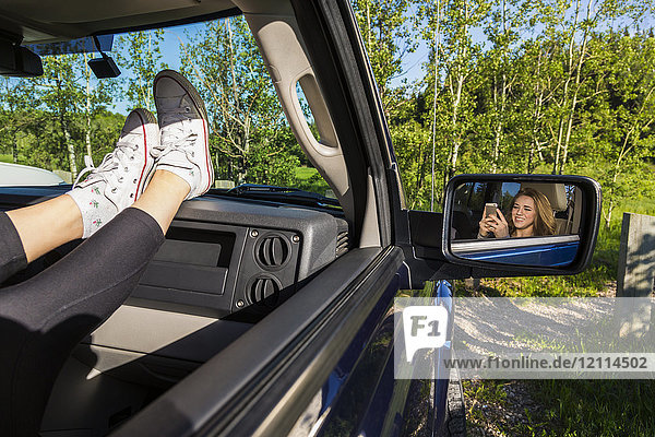 Young woman using her cell phone in a passenger seat in a vehicle; Edmonton  Alberta  Canada