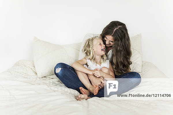 Portrait of a mother and young daughter sitting on a bed spending time together and laughing; Sorrento  British Columbia  Canada