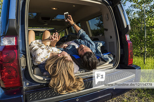 Young couple laying in the back of their packed vehicle on a road trip  showing their boots and using their cell phone; Edmonton  Alberta  Canada