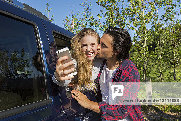 A young couple taking a self-portrait with their smart phone at their vehicle while he kisses her on the cheek; Edmonton  Alberta  Canada