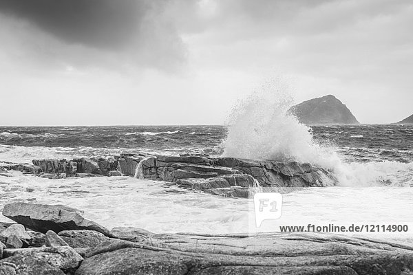Black and white image of waves splashing against rocks at the shore along the coast of Norway