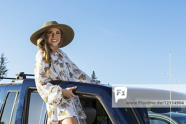 Young woman with long blond hair and hat posing for the camera at the open door of a vehicle; Edmonton  Alberta  Canada