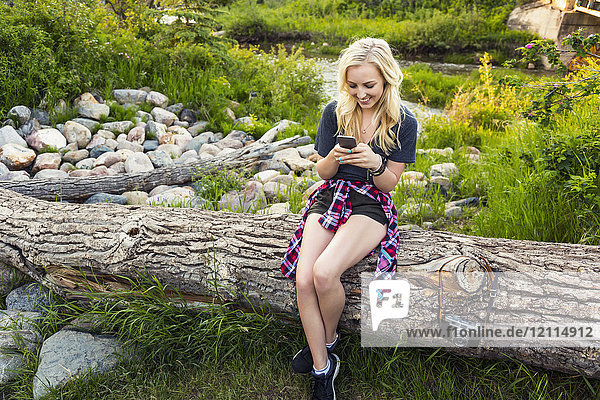 A young woman sits on log in a park using her cell phone with a river in the background; Edmonton  Alberta  Canada