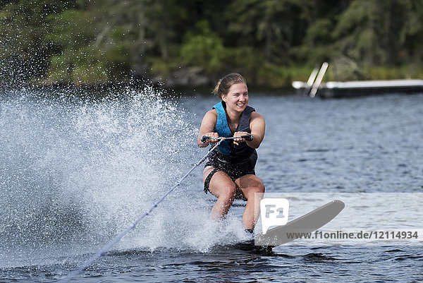 A young woman wakeboarding behind a boat on a lake; Lake of the Woods  Ontario  Canada