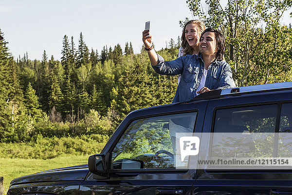 Young couple taking self-portraits with a cell phone while standing up in their sunroof of their vehicle; Edmonton  Alberta  Canada