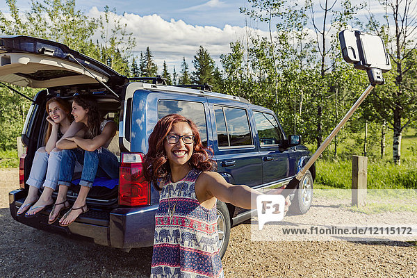 Two young women on a road trip sit in the back of a vehicle talking and laughing together while a friend takes a selfie with a selfie stick; Edmonton  Alberta  Canada
