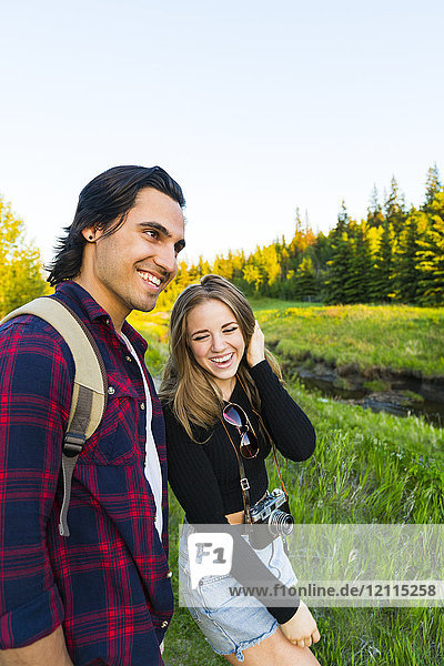 Young couple walking together in a city park in autumn taking a camera with them on the adventure; Edmonton  Alberta  Canada