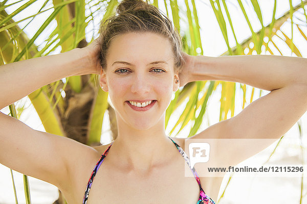 Portrait of a young caucasian woman in a bikini top with a tropical tree in the background; Negril  Jamaica