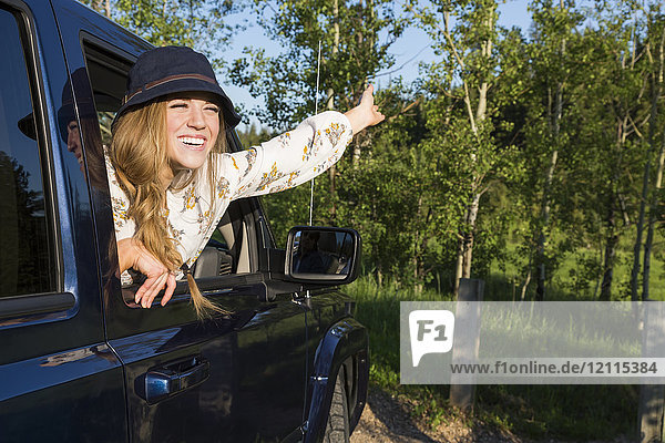Young woman wearing hat leaning out open vehicle window with a big smile and arm raised to the sky; Edmonton  Alberta  Canada