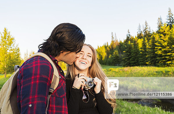 Young couple walking together in a city park  the young woman holding a camera and the young man kissing her cheek; Edmonton  Alberta  Canada