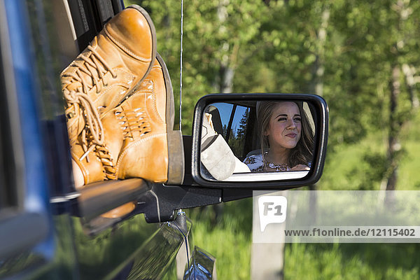 A female passenger with her feet out the window of the vehicle during a rest stop on a road trip; Edmonton  Alberta  Canada