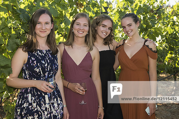 Portrait of four young women dressed in formal wear and holding glasses with drinks; Cobble Hill  British Columbia  Canada