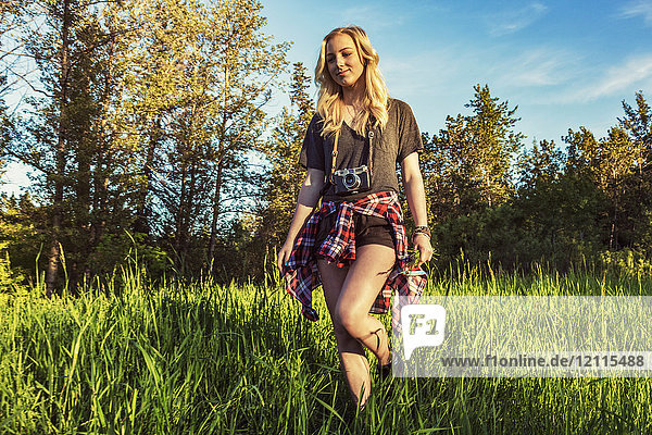 A young woman with long blond hair walks in the grass towards the camera with a camera around her neck; Edmonton  Alberta  Canada