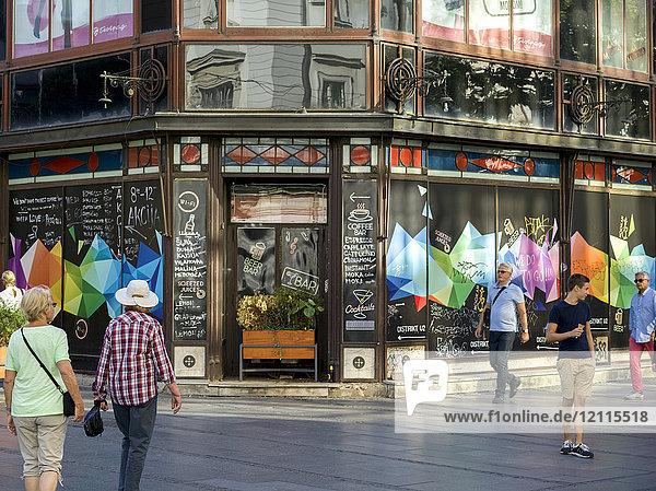Pedestrians walking on the street with a restaurant in the corner building; Belgrade  Vojvodina  Serbia