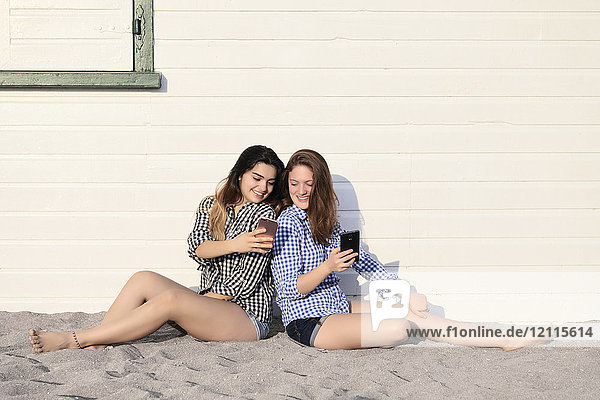 Two teenage girls sitting in the sand against a building looking at their smart phones together  Woodbine Beach; Toronto  Ontario  Canada